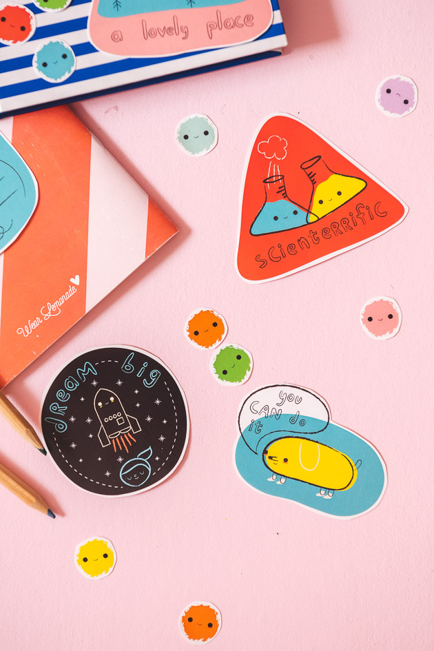 Stickers and a notebook on a pink backdrop