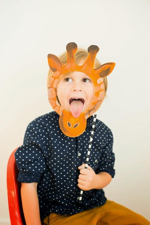 Little boy wears giraffe mask.