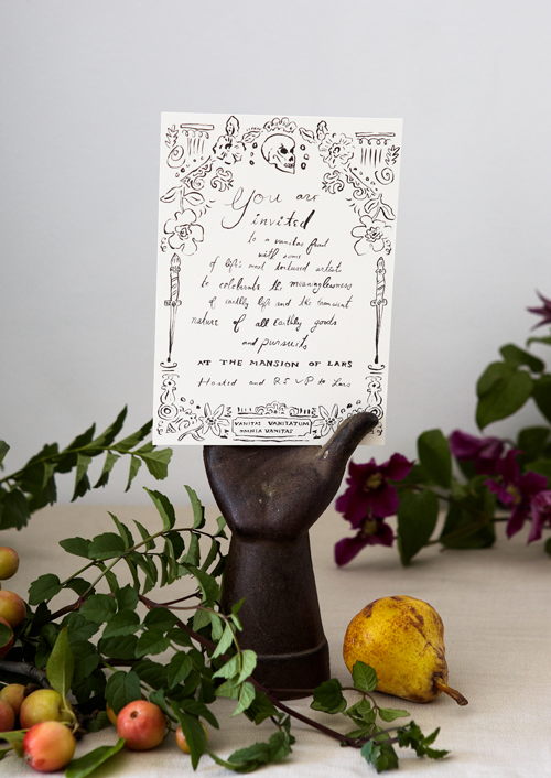black and white illustrated halloween party invitation in a black decorative hadn surrounded by foliage and fruits