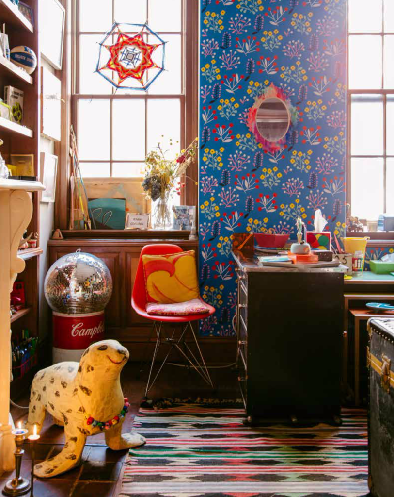 A brightly-colored room with blue floral wallpaper, a colorful rug, bright pillows, and lots of knickknacks around.