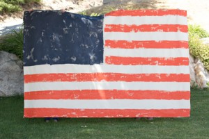 A painted american flag picnic blanket outside.