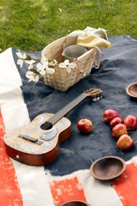 a guitar, peaches, and a picnic basket with dogwood flowers on a painted american flag picnic blanket.