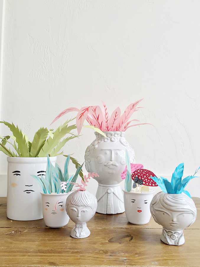 Paper plants in faces vases