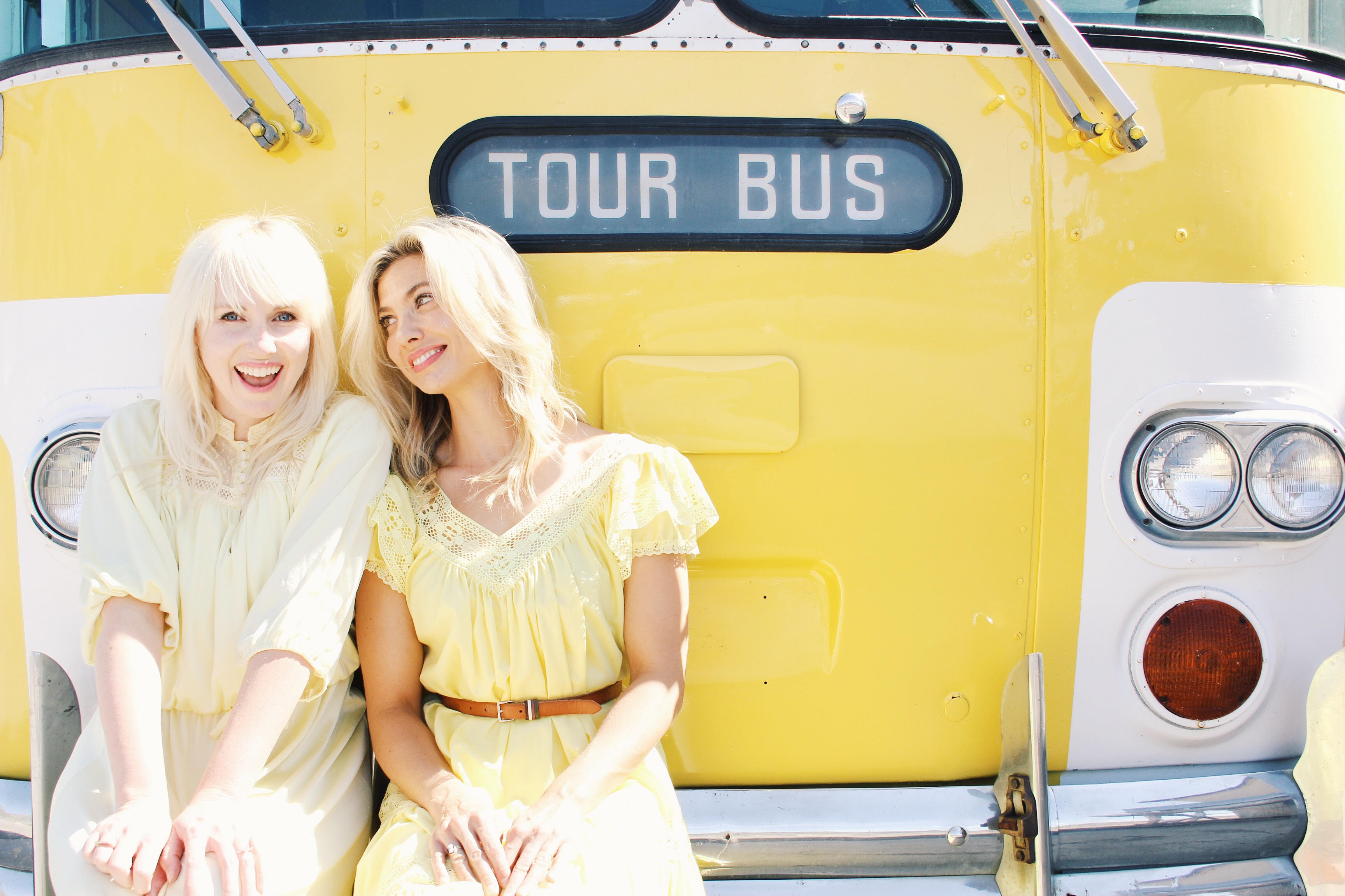 Mindy Gledhill in Dress the Rainbow in front of her yellow tour bus