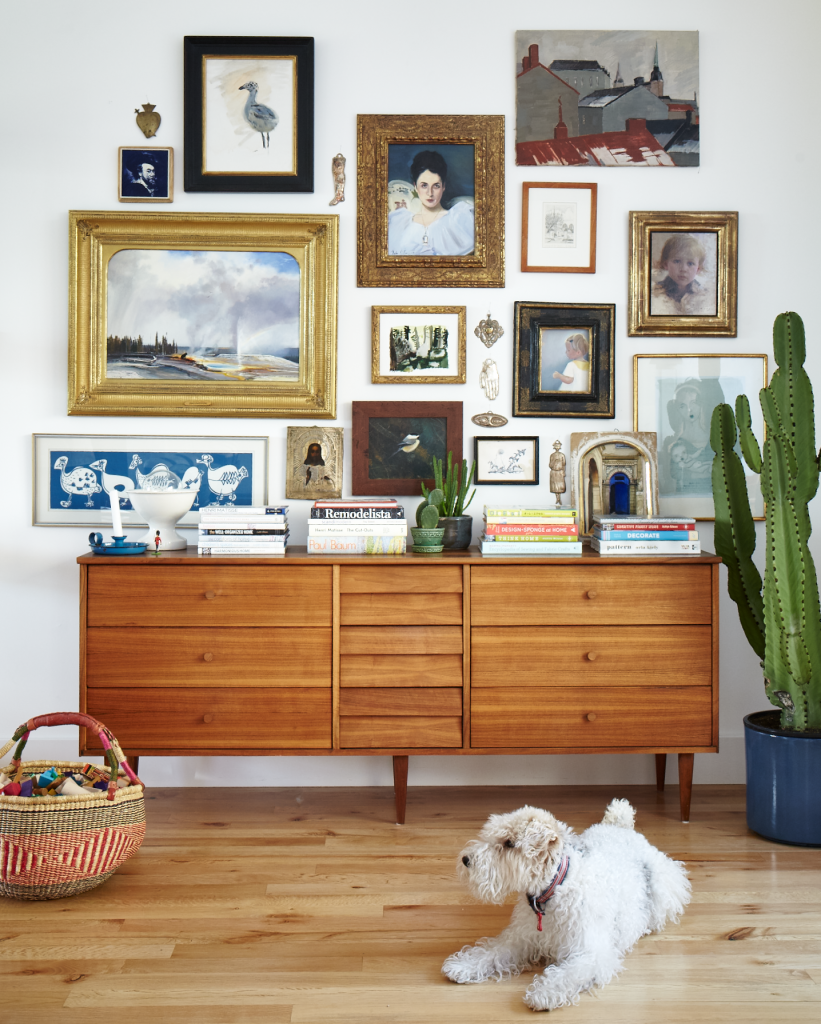 Gallery wall above a brown dresser with a cute white dog in front.