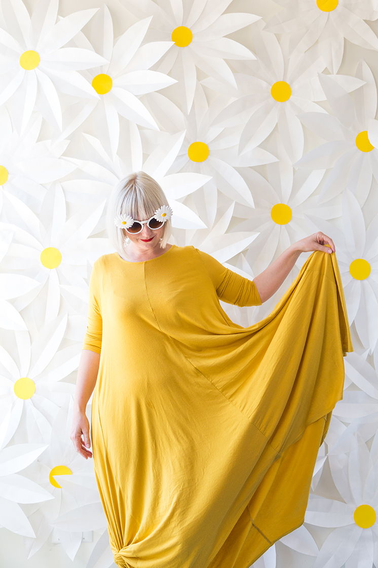 Brittany stands in front of a paper daisy-covered wall wearing a yellow dress.