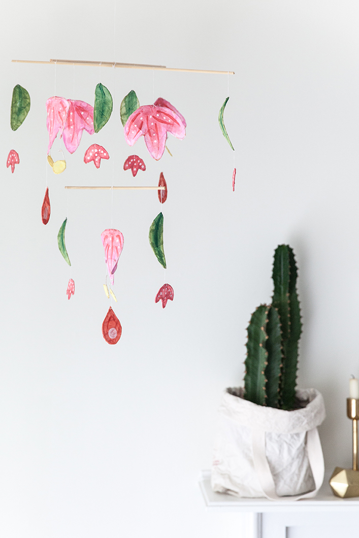 A paper mobile hangs in a white room with a cactus