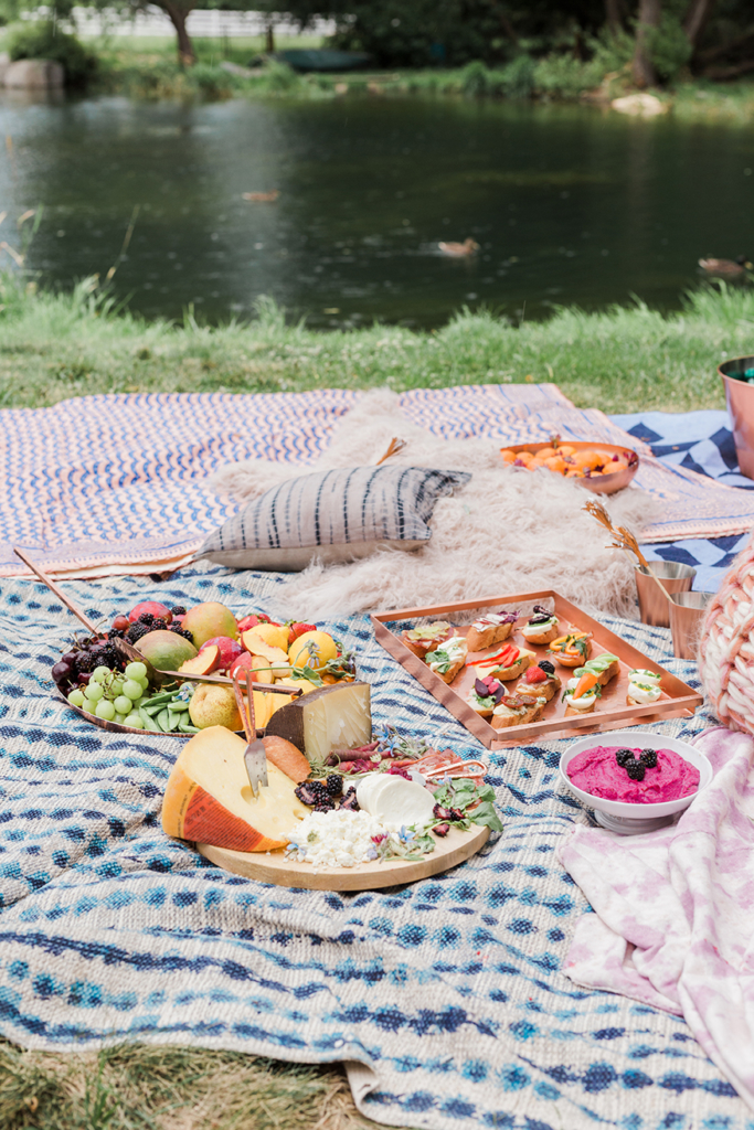 A fancy summer picnic next to a pond.