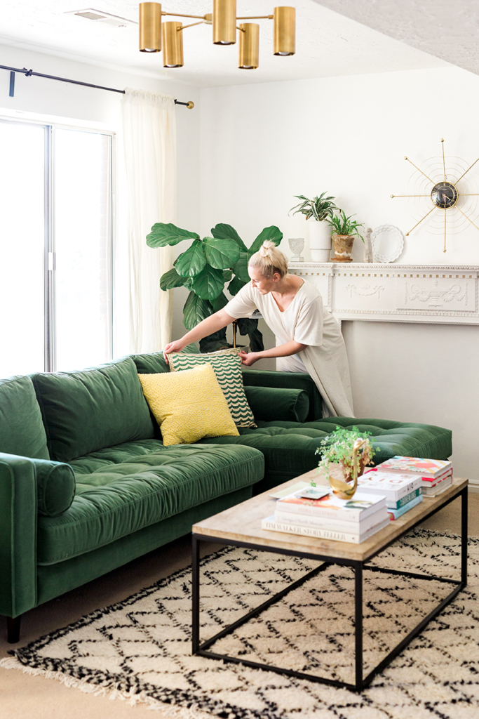 Brittany adjusts pillows on a beautiful green sofa in a light-filled room