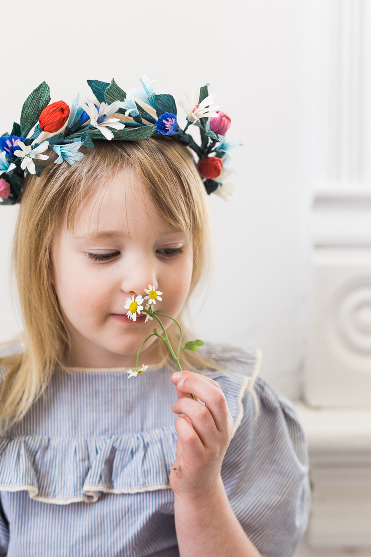 A little girl wears a paper flower crown and smells some little flowers.