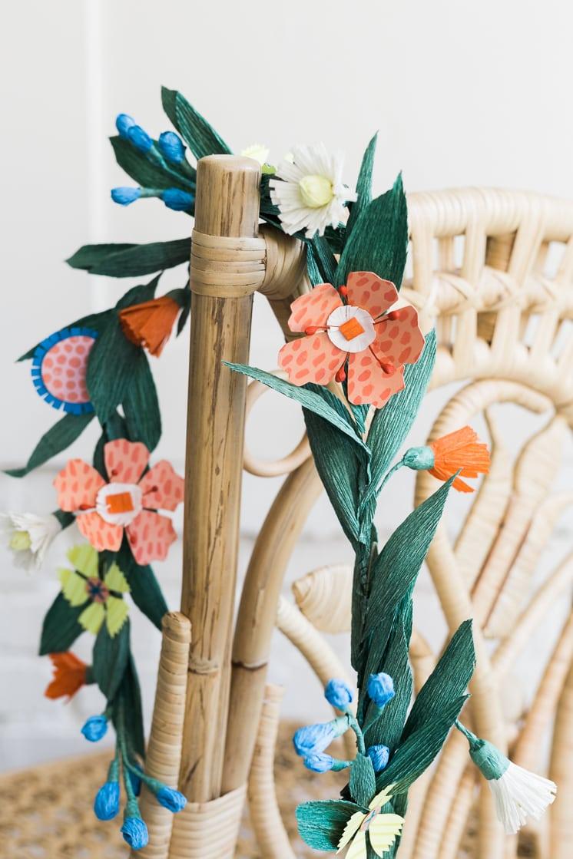 Paper flower garland hangs over a rattan chair