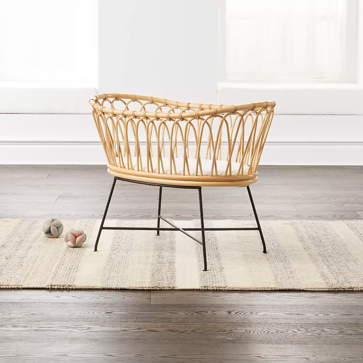 A rattan bassinet with metal legs in a light-filled nursery