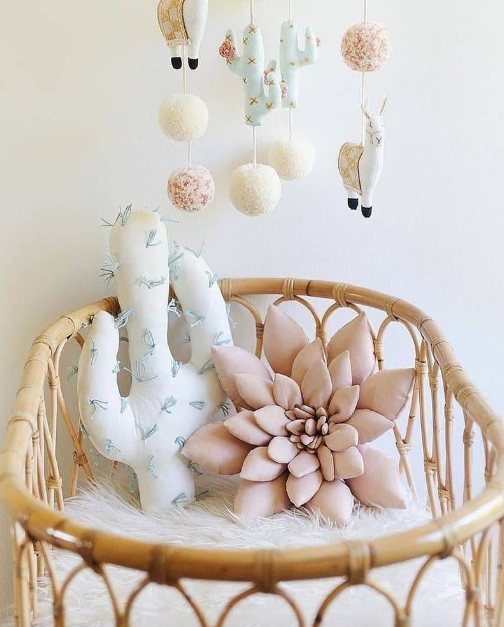 Rattan Bassinet with plush cactus and lotus flower inside.