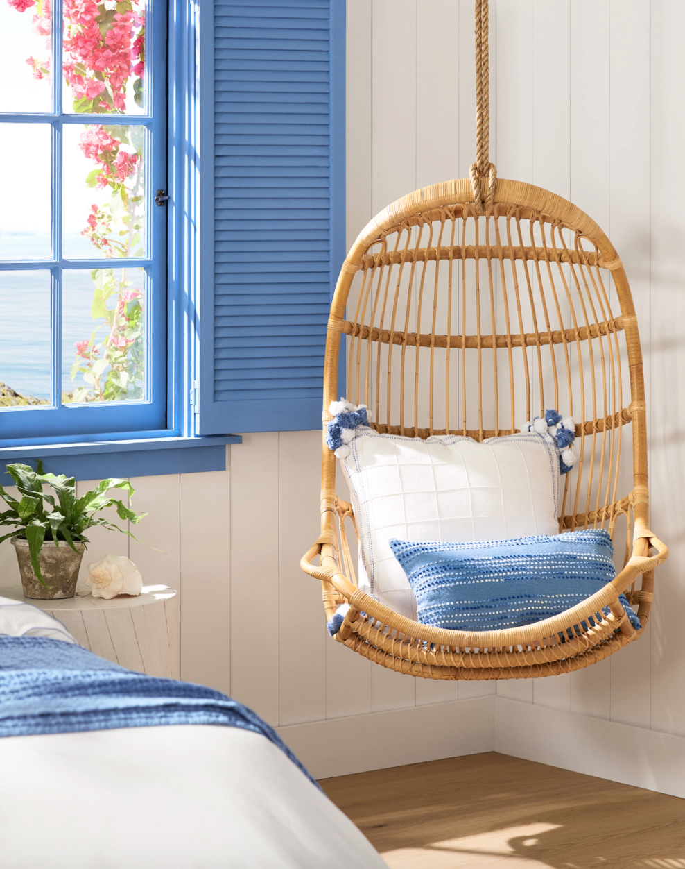 Rattan hanging swing in a light-filled room with blue pillows and accents