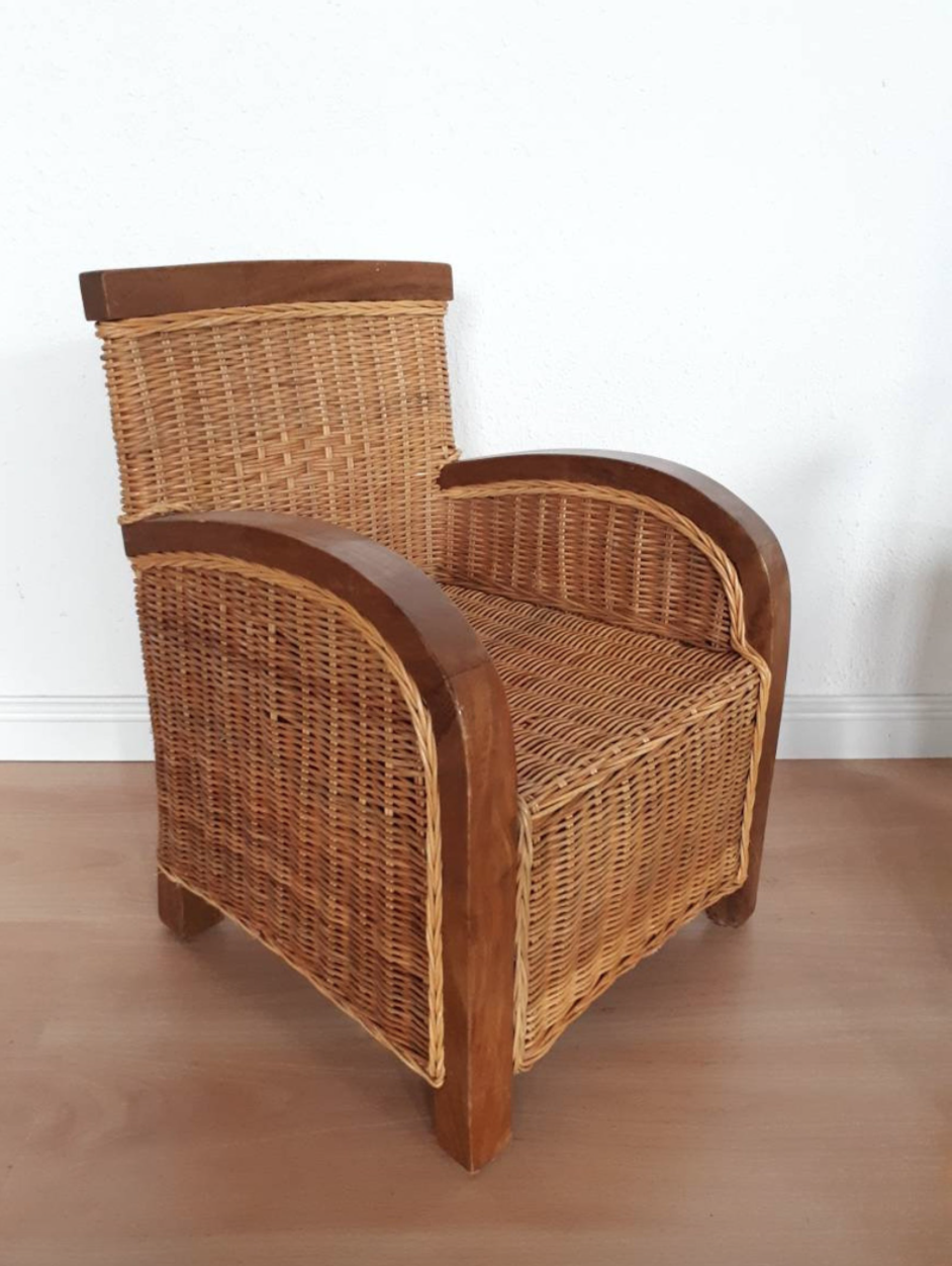 A rattan and teakwood antique armchair for kids in a white room.