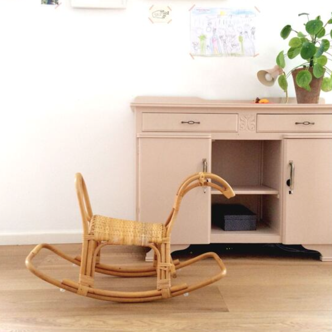 Rattan rocking horse in front of a cabinet.