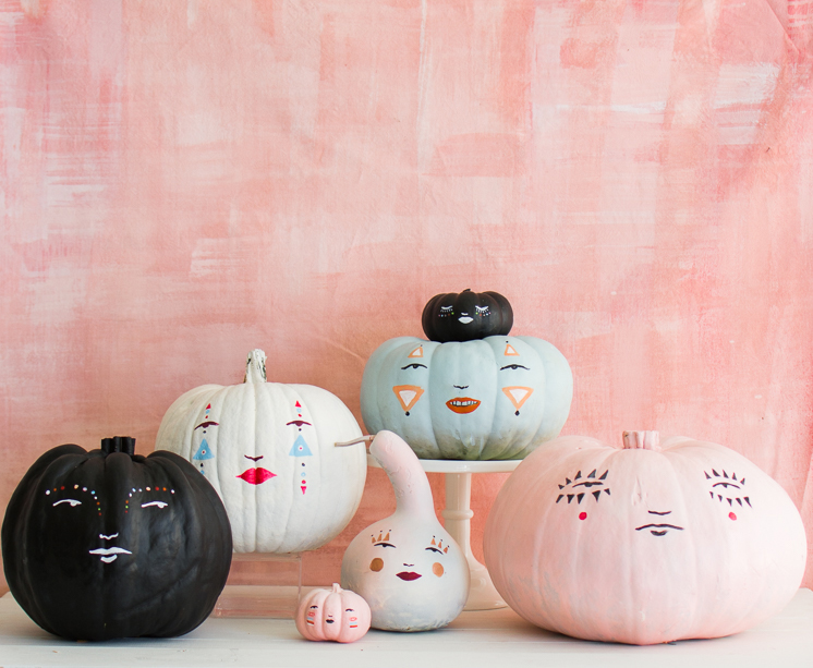 painted pastel pumpkin faces against a pink background