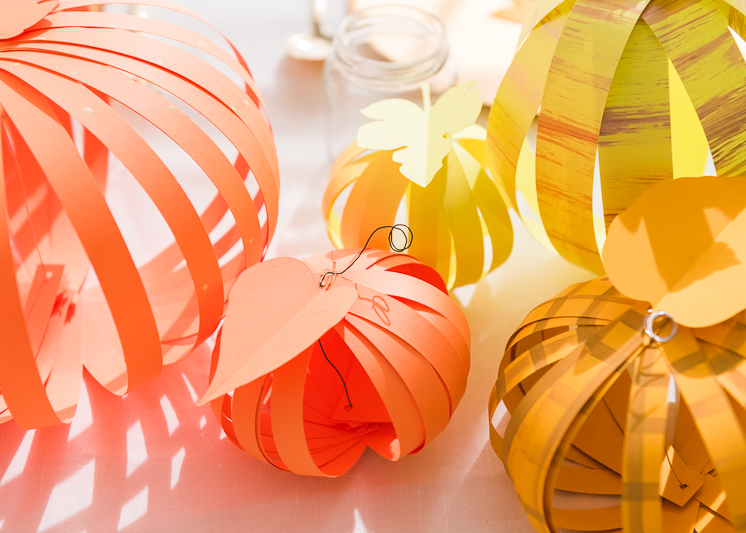 orange, gold, and yellow paper pumpkins on a table setting.