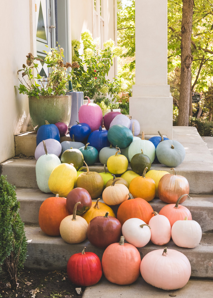 Rainbow pumpkins arranged on a porch.