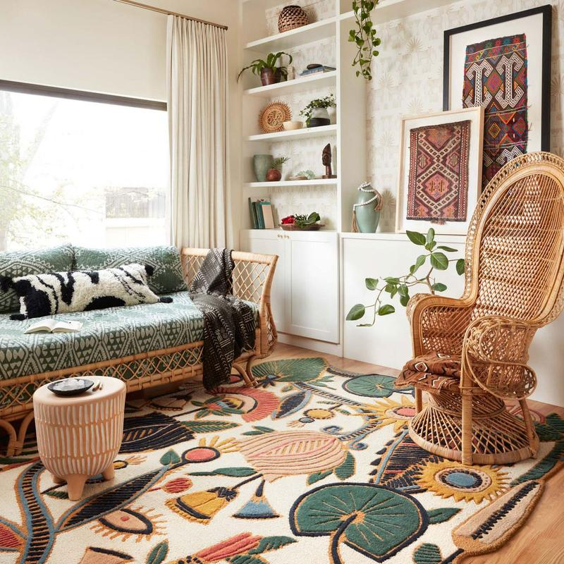A brightly-lit room with a modern rug by Jungalow. The room has shelves, plants, a wicker rocker, a big window, and a sunbed.