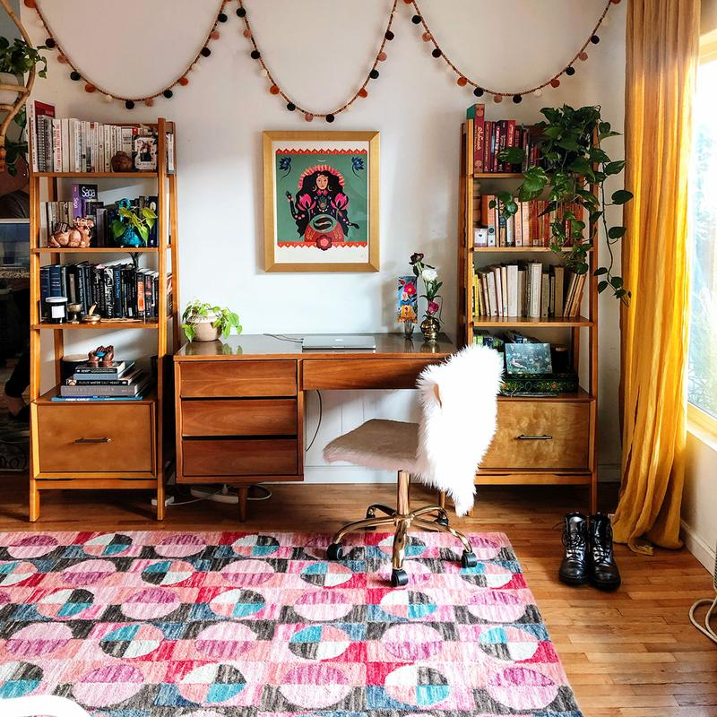 A colorful bohemian room with a pink, cyan, and blue rug, yellow curtains, and warm wooden furniture.