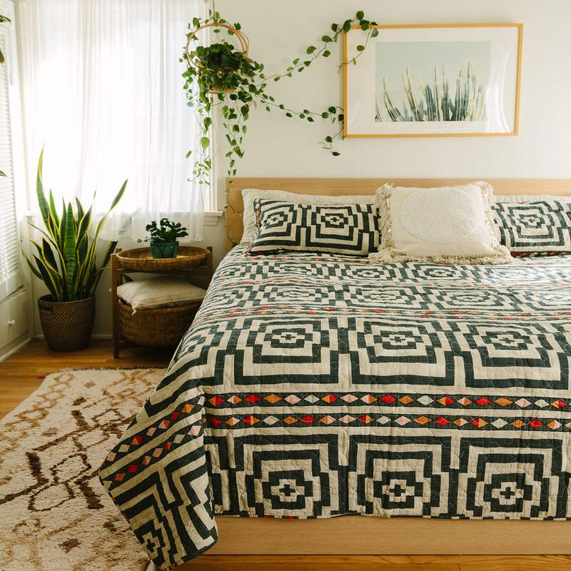 A Jungalow hypnotic quilt set on a light wood bed. The space has windows and plants and is airy and funky at the same time.