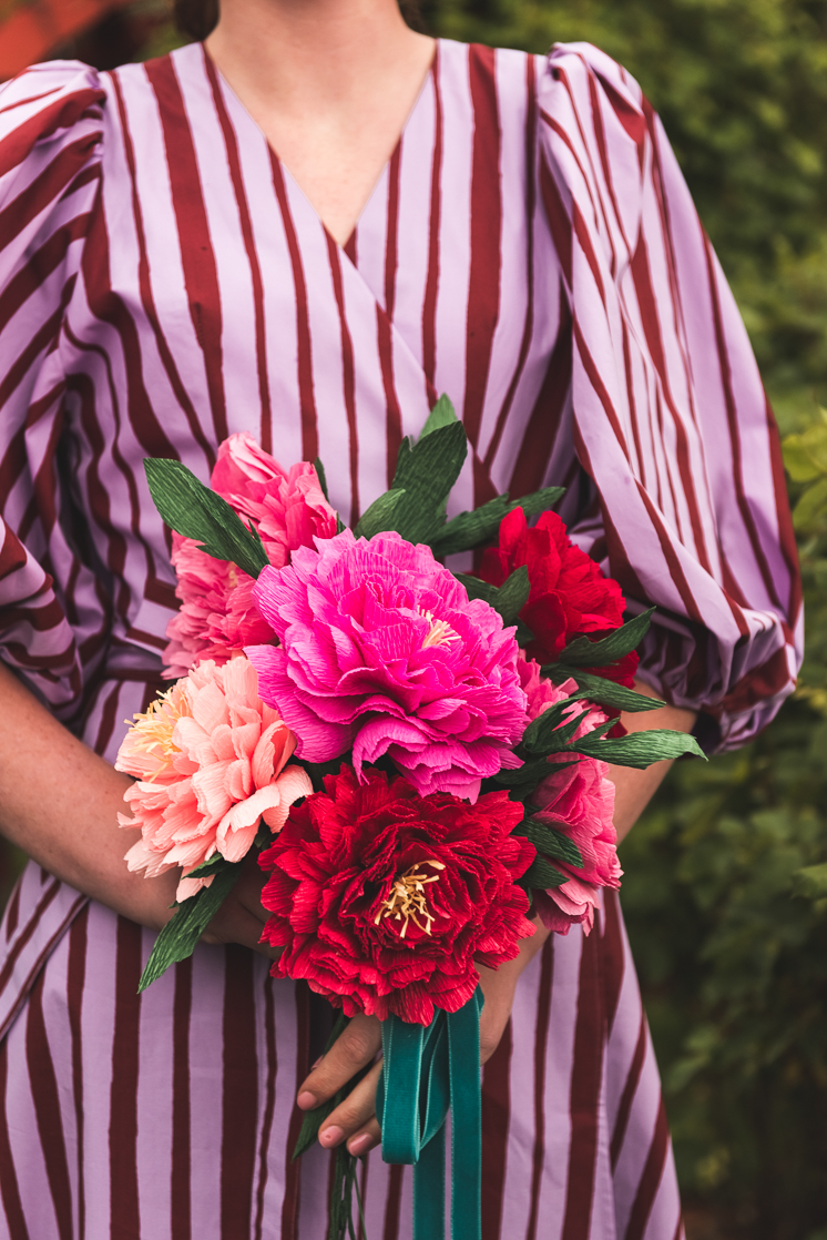 Paper peony bouquet held by a person in a striped dress