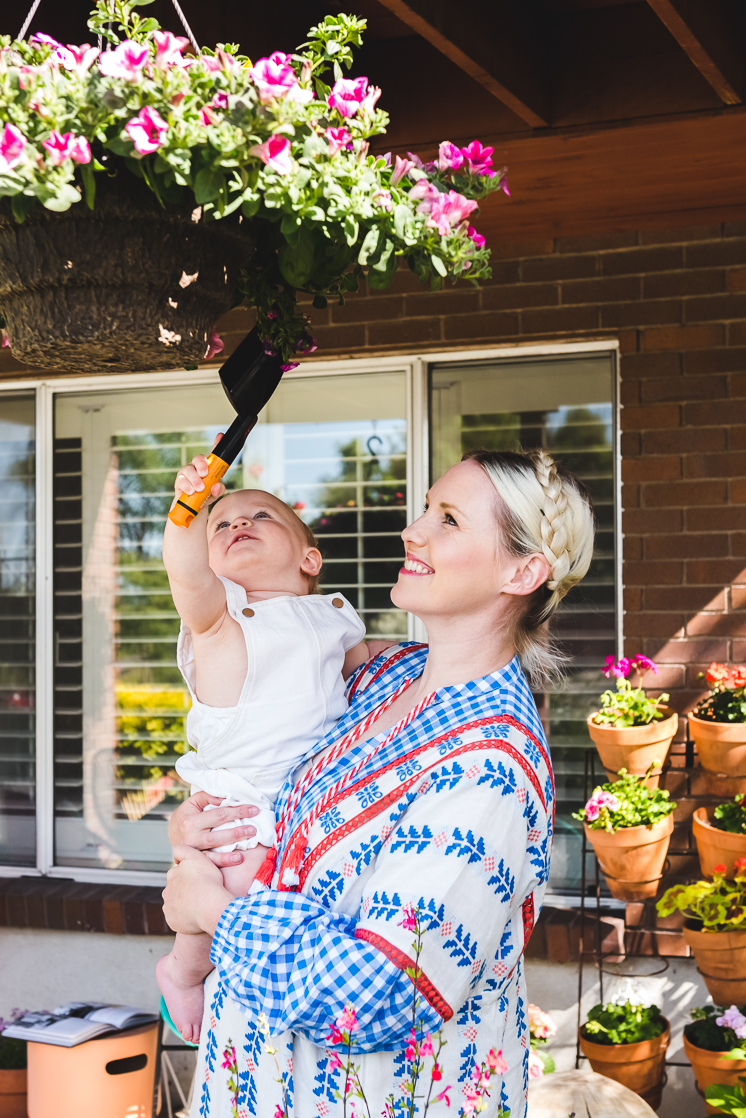 Brittany holds baby Jasper up to a hanging flower pot full of pink flowers.