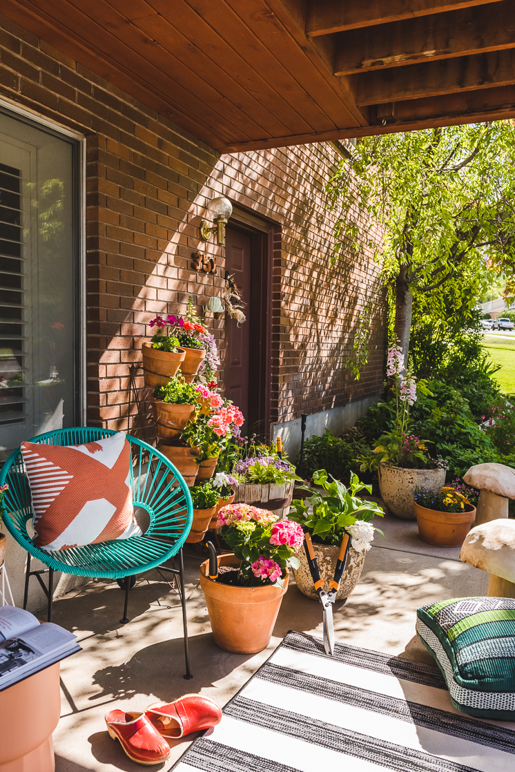 An exterior shot of a porch container garden with lots of flowers and sunlight.