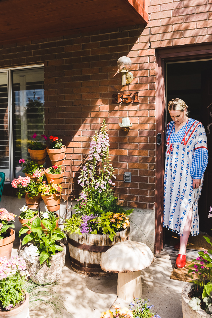 Brittany steps out the door to a porch garden full of container plants in bright colors.