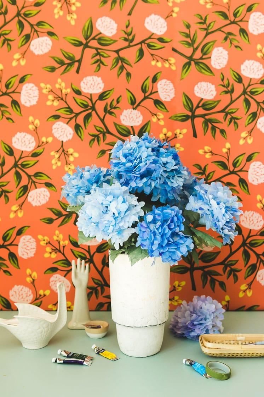 Paper hydrangeas in a white vase against a floral orange background