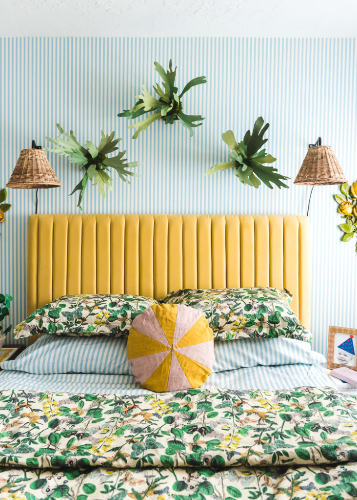Interior shot of a bedroom with blue and white striped wallpaper. There's a yellow headboard, green floral bedding, paper staghorn ferns, and wicker lamps.