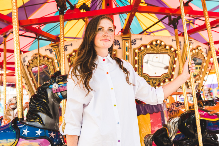 a white woman with brown hair wears a white blouse with rainbow buttons. She's standing in front of a carnival carousel.