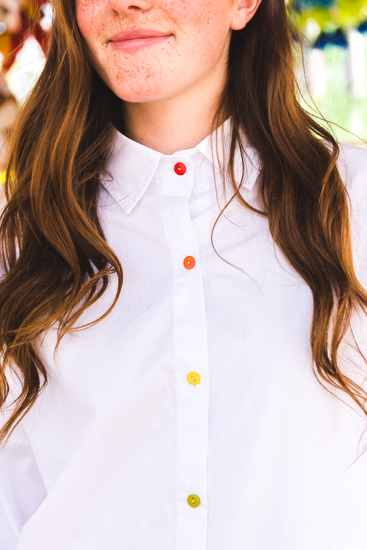 a white woman with brown hair wears a white blouse with rainbow buttons