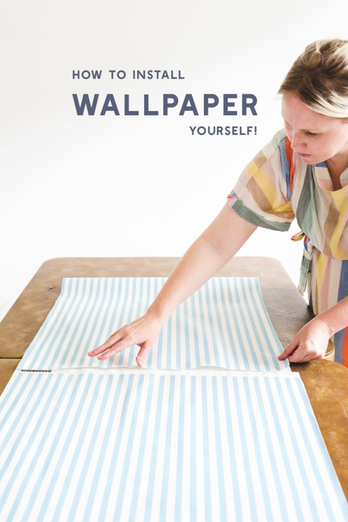 """Brittany works on installing blue and white striped wallpaper with text that reads """"how to install wallpaper yourself"""""""