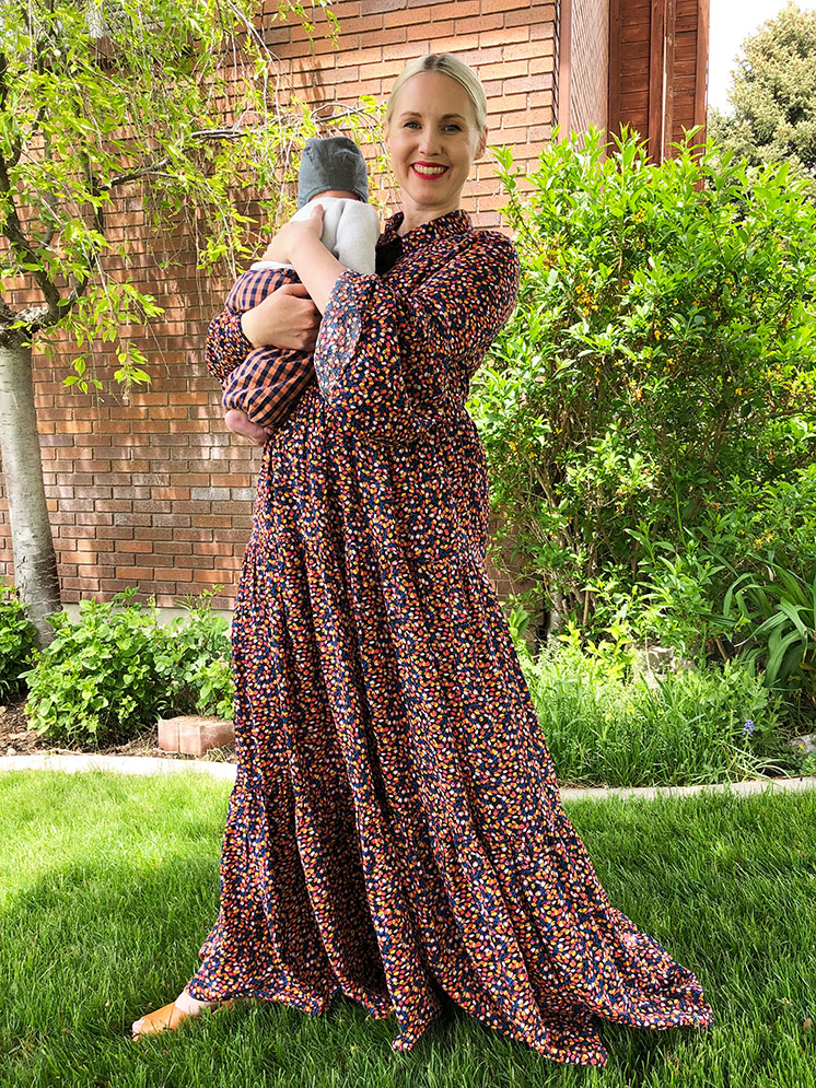 Brittany wearing a long floral dress and holding a baby