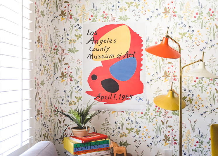 A colorful lamp in a room with wildflower wallpaper and a LACMA exhibition poster