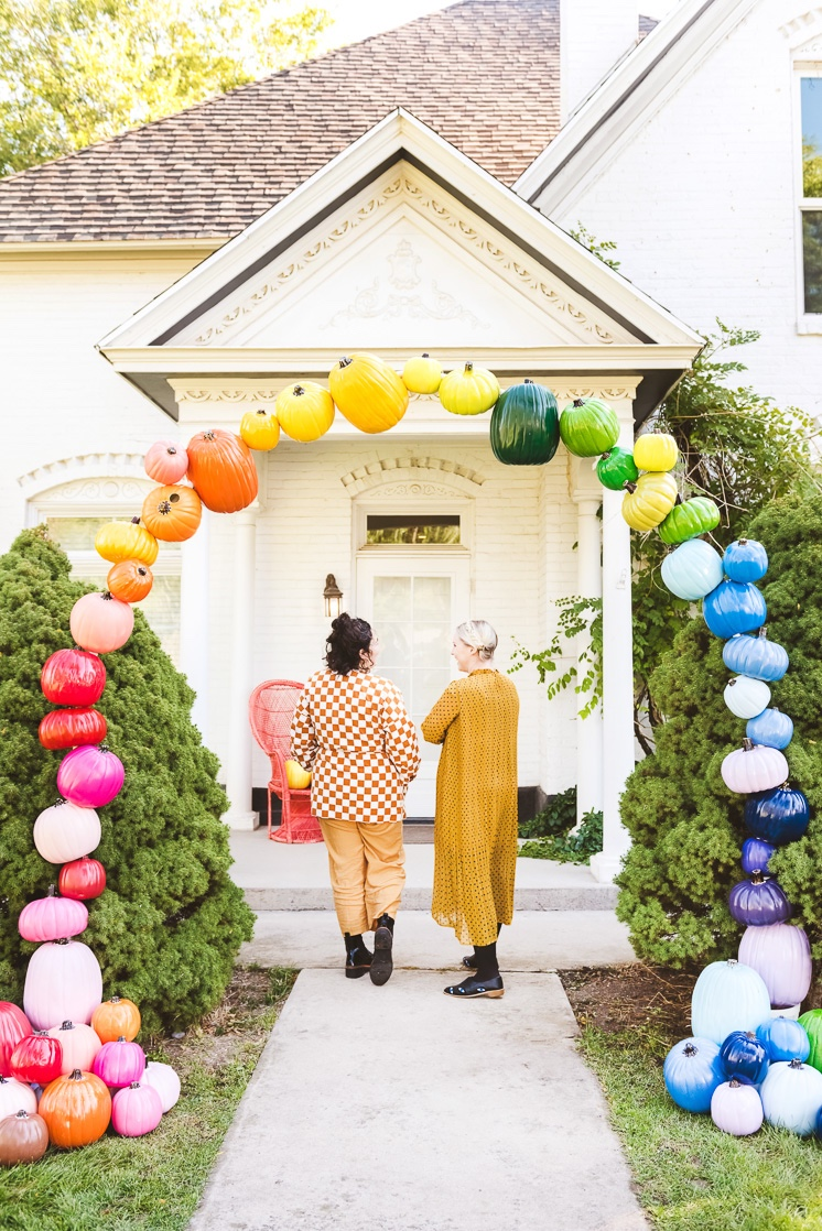 Brittany and Sammy wearing yellow and walking under a rainbow pumpkin arch
