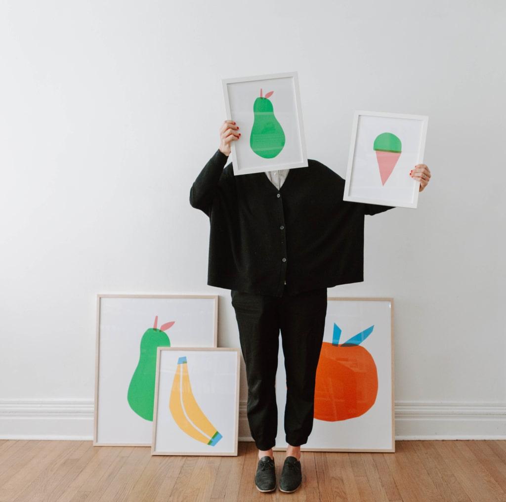 Amanda Jane Jones holding up her prints from the Lars Print Shop