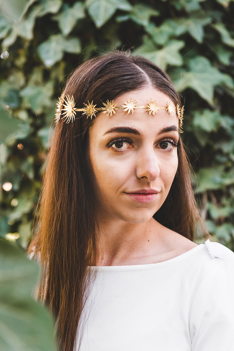Hailey wearing a white top and a gold star crown.