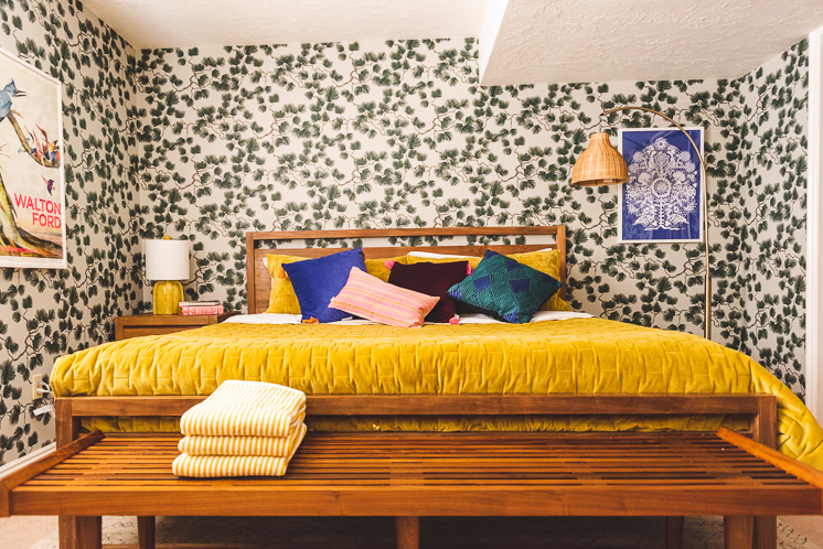 a room with pine-themed wallpaper. There are pillows in dark blue, pink, green, and black, the bed is warm wood with a mustard duvet, and there's a wicker lamp in the corner. There's also a blue art print on the wall.