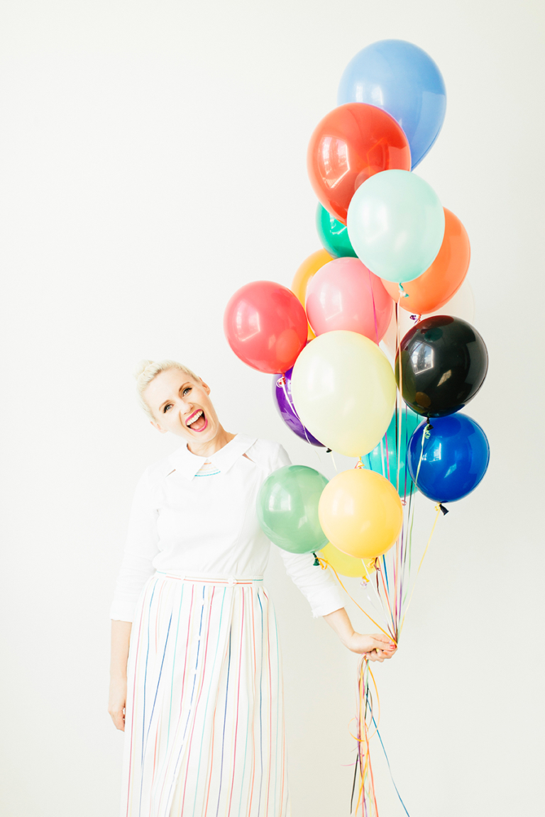 Brittany wearing a white dress and holding a bundle of rainbow balloons