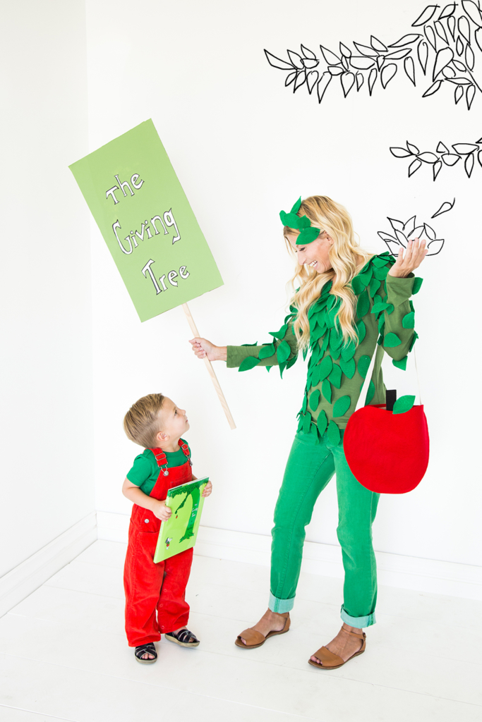 A mom wearing a green outfit with leaves and holding a felt apple bag stands next to her child in red overalls. They're dressed as the Giving Tree.