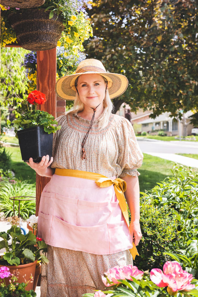 Brittany stands in the garden wearing an apron and a sun hat and holding a geranium.
