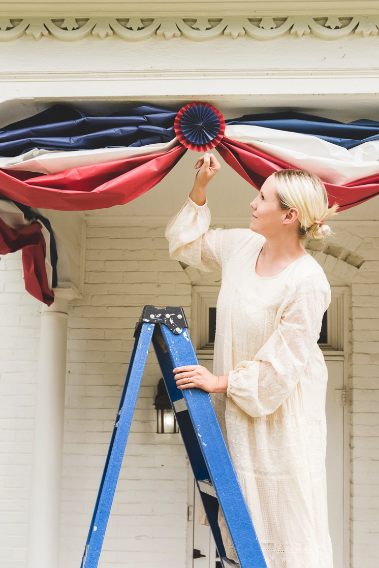 Brittany stands on a ladder and puts up red, white, and blue paper bunting on a white house.