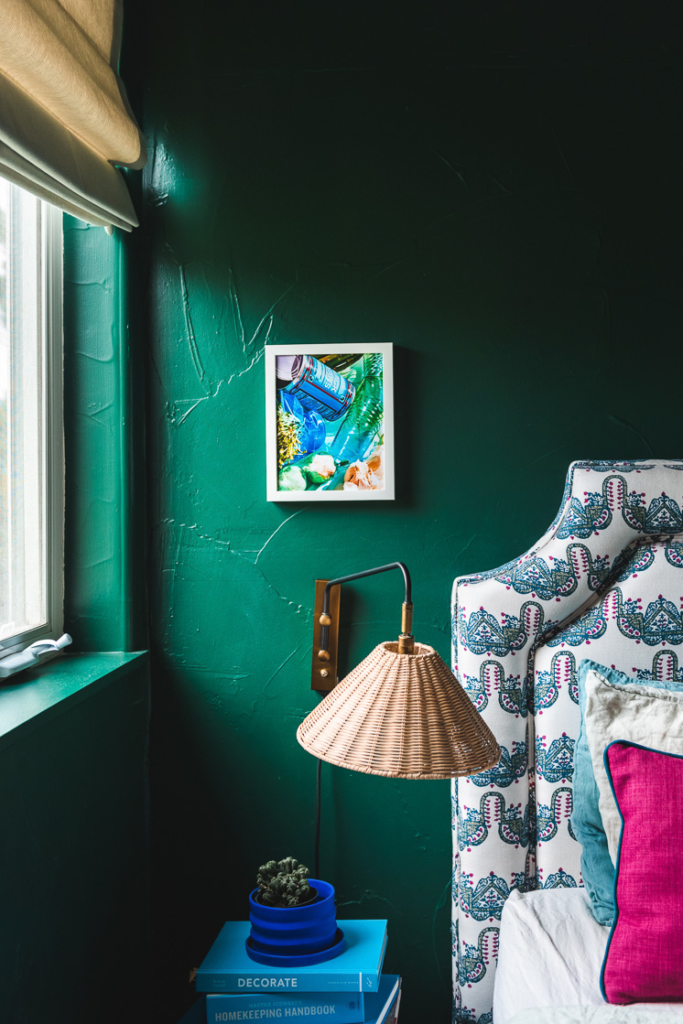 a chaunte vaughn photo hanging against a textured green wall above a lamp by a headboard.