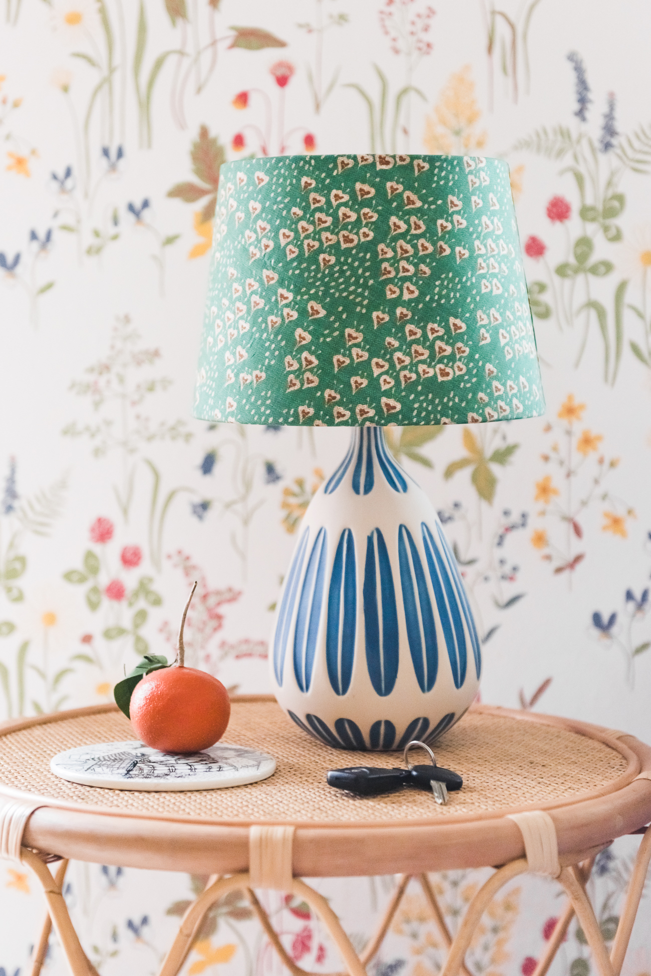 Lamp customized with spoonflower fabric from Holli Zollinger against a wildflower covered wall.