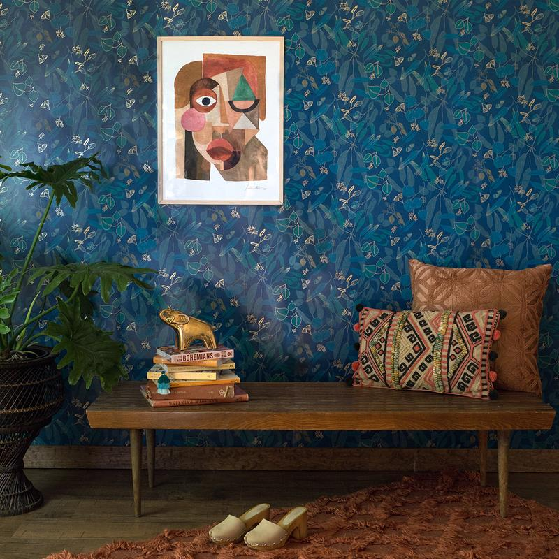 An interior photo. The wall is blue floral wallpaper, there's a big houseplant, a patterned rug, and pillows propped on a wooden bench.