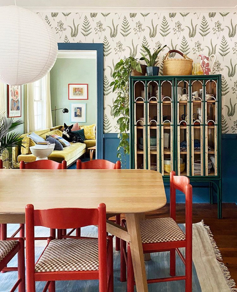 Interior shot of a colorful, eclectic dining room with red chairs, wallpaper and blue wainscoting, a green cabinet, and plants.