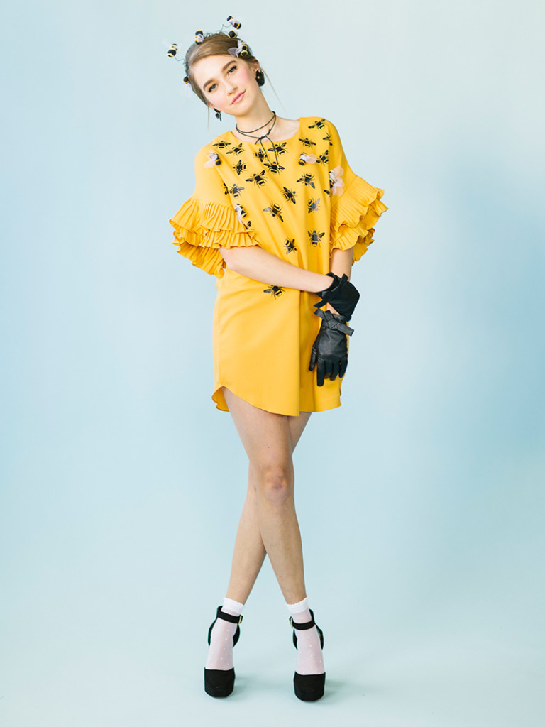 a white woman wearing a yellow dress with iron-on bees, black gloves, a bee headband, and black shoes stands in front of a blue background.